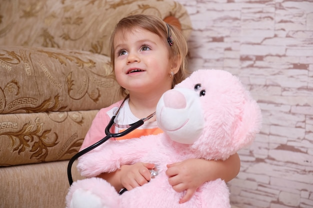 Adorable child playing doctor or nurse with plush toys at home.