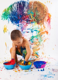 Adorable child playing with paints