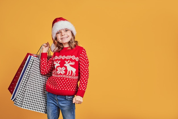 Adorable child in red santa hat and sweater with deer carrying colorful shopping bags with christmas gifts on yellow background