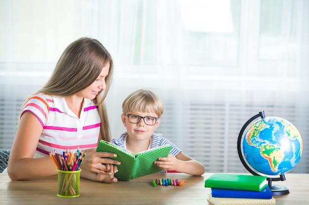 Прелестный ребенок учится с его матерью на дому. семья вместе делать домашнее задание. молодая мама помогает сыну научиться заданию.