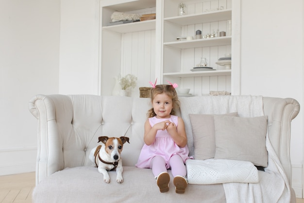 Adorable child with dog on sofa