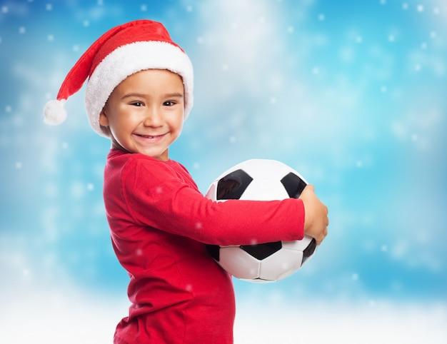 Adorabile bambino con il cappello della santa che mostra la sua palla