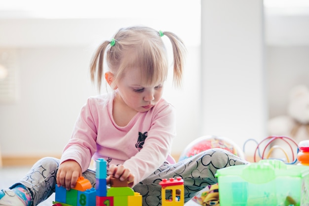 Adorable child with toys in playroom
