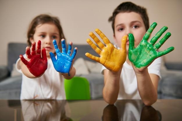 愛らしい子供たち、男の子と女の子、カメラに赤、青、黄色、緑のペンキで描かれた手を見せています。
