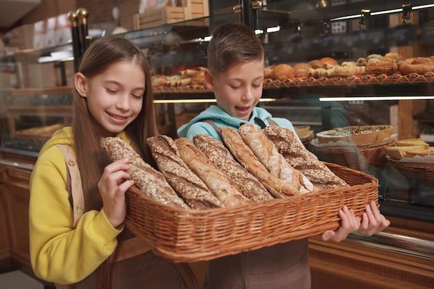 가족 비즈니스 빵집에서 일하는 것을 즐기고 맛있는 신선한 빵을 시음하는 사랑스러운 아이들