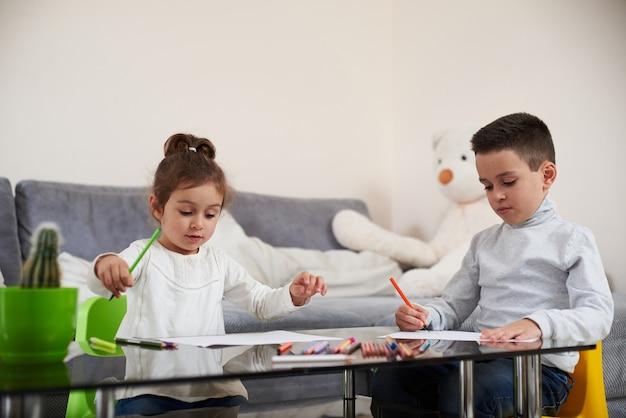 테이블에 앉아 컬러 연필을 사용하여 그림 사랑스러운 아이들. 가정에서의 교육의 개념