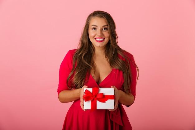 웃고 선물 상자를 들고 빨간 드레스를 입고 사랑스러운 통통한 여자 20 대
