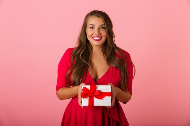 Adorable chubby woman 20s wearing red dress smiling and holding gift box