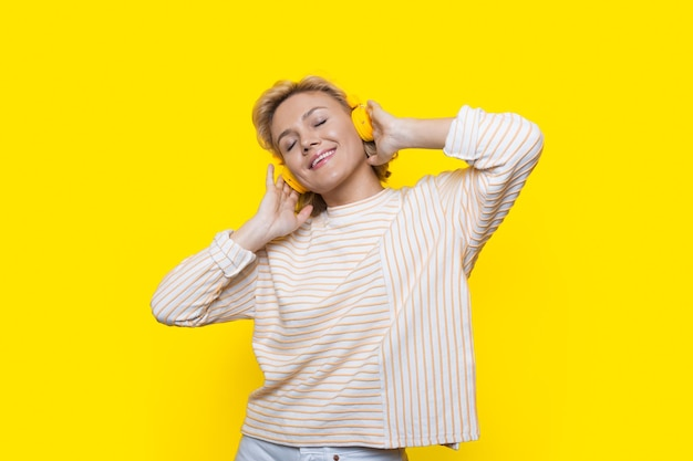 Adorable close up photo of a blonde lady who is listening to musing and enjoying time on a yellow studio wall