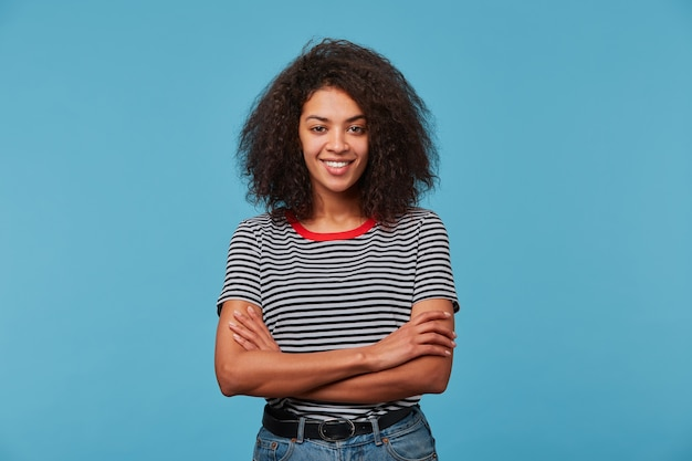 Adorable confident happy young woman with playful look has afro hairstyle laughing smiling against blue wall