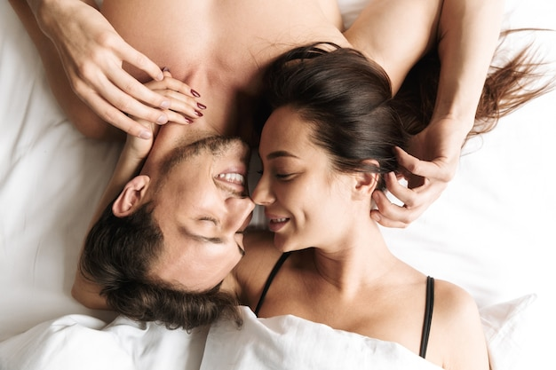 Adorable couple 30s hugging together, while lying in bed at home or hotel apartment