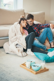 Adorable couple are embracing on the floor near the couch before eating cereals with milk