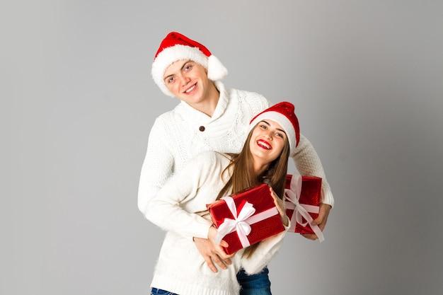 사랑스러운 커플 회색 벽에 스튜디오에서 선물로 크리스마스를 축하