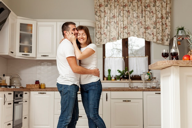 Adorable couple embracing in kitchen