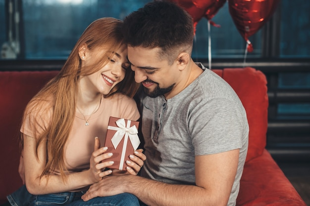 Adorable couple embracing and smile on a couch holding a present and air balloons