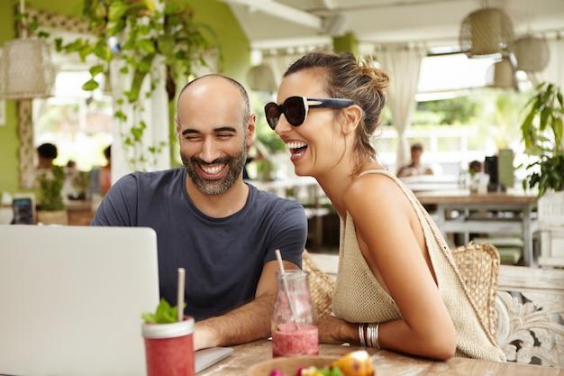 Очаровательная пара громко смеется, сидя в летнем кафе со своим современным ноутбуком и просматривая фильмы онлайн, используя бесплатный wi-fi.