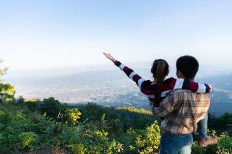 丘の上の自然の中で晴れた日に愛らしいカップル
