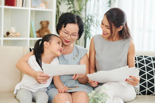 Очаровательная креативная маленькая девочка показывает свои рисунки маме и бабушке, когда они сидят на диване дома