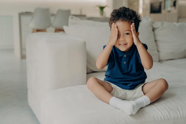 快適な大きな白いソファに座って遊ぶ準備ができて、数えたり目を覆ったりするのをやめて、かくれんぼのゲームで探しに行くカジュアルな服装の愛らしいカーリーアフロアメリカンボーイ