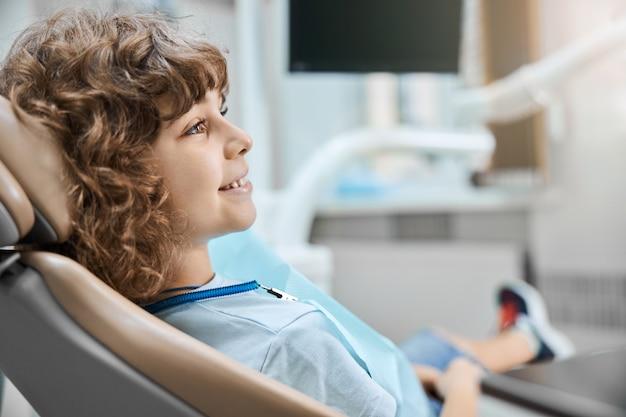 병원에서 regualr 치과 검진 중에 웃고있는 사랑스러운 곱슬 머리 아이