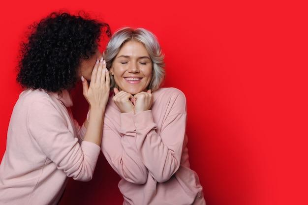 Очаровательная кудрявая женщина что-то шепчет своей сестре-блондинке на красной стене с свободным пространством