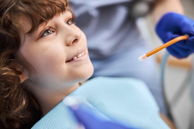 입 근처에서 타액 배출기로 치과 치료를받는 동안 웃고있는 사랑스러운 곱슬 아이