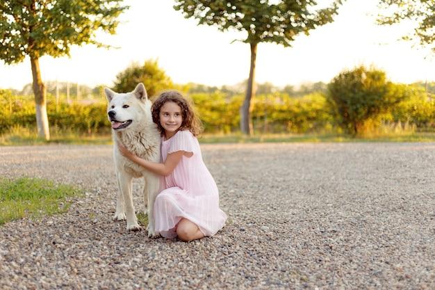 公園で大きな白い犬と一緒に愛らしい巻き毛の女の子。ピンクのドレスを着た美しい7歳の女の子が、夏の散歩中にお気に入りの犬を抱擁します。