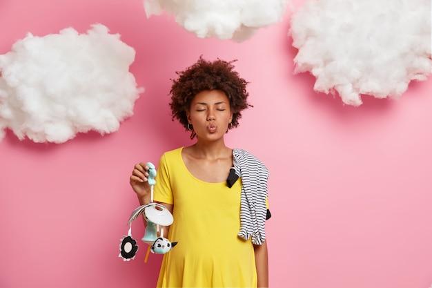 唇を折りたたんだ愛らしい巻き毛の女性の未来のママは、快適な服を着て、未来の赤ちゃんの性別を見つけ、携帯を運び、ピンクの壁に子供服を立てます。親子関係の貴重な瞬間