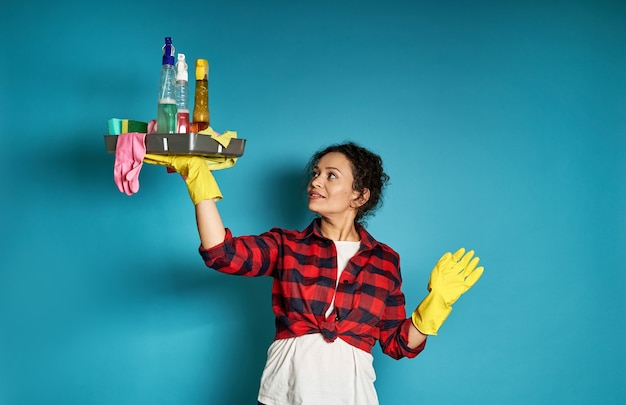 手にクリーニング用品のトレイと腕を上げ、青を見上げる黄色のゴム手袋の愛らしい巻き毛の女性