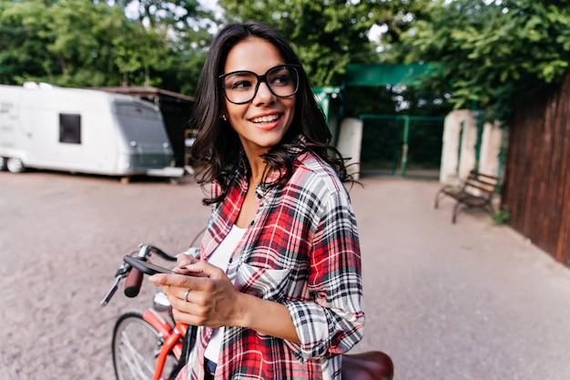 전화 둘러보고 사랑스러운 곱슬 여자입니다. 도시에서 시간을 보내는 귀여운 유럽 여자의 야외 초상화.
