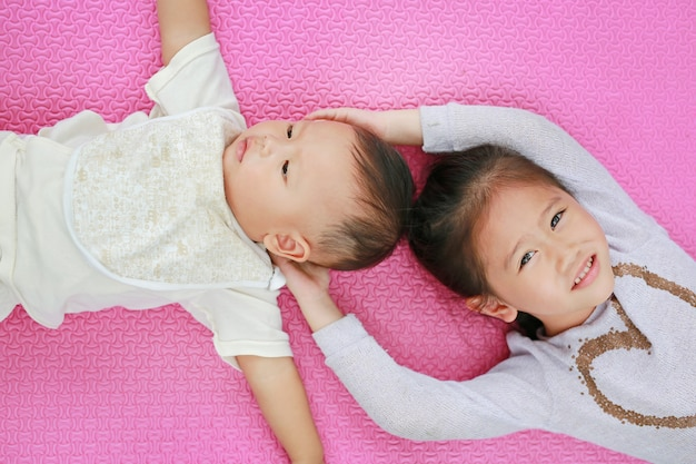 Adorable cute asian sister and little brother lying on pink mattress mat looking at camera.