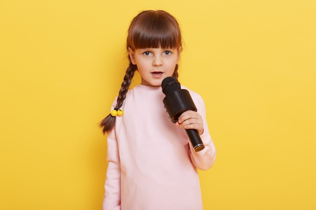 Adorable cute child with microphone in hands singing songs, looks at camera, performing isolated over yellow background, child arranging concert, sings in karaoke.