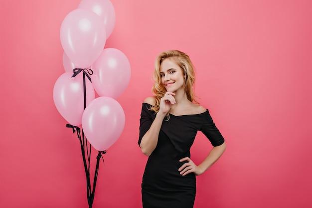 그녀의 생일에 포즈를 취하는 금발 물결 모양의 머리를 가진 사랑스러운 귀여운 소녀. 블랙 핑크 벽에 고립 된 즐거운 젊은 여자의 초상화. 무료 사진