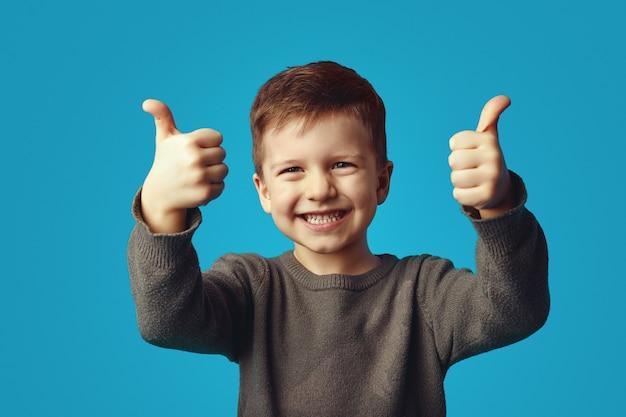 Очаровательный милый ребенок поднимает руки показывает палец вверх жест счастливо смеется