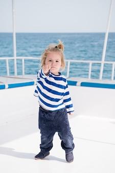 여름 유람선에서 보트나 요트를 탄 사랑스러운 작은 아기 선장. 여행 모험, 가족 휴가에 아이와 요트. 선원 스타일, 해상 패션의 아이 벗겨진 해양 의류