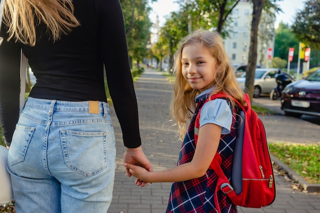 Adorable cute little girl feeling excited about going back from school with her mother by the hand