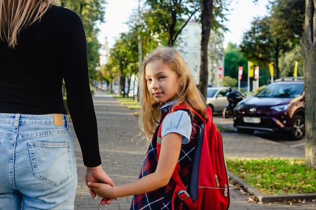 手で母親と一緒に学校から戻ることに興奮している愛らしいかわいい女の子
