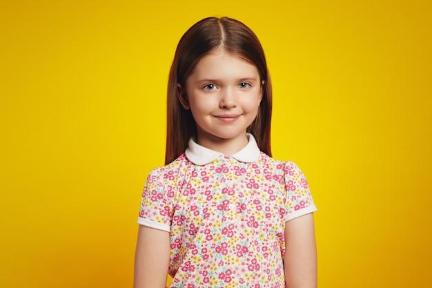 Очаровательная милая маленькая девочка в летней одежде на желтом фоне