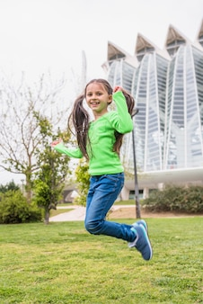 사랑스러운 귀여운 소녀 잔디에 점프