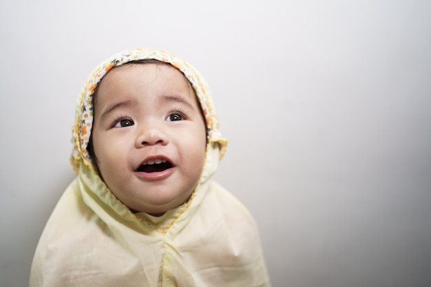 Adorable cute little girl wearing muslim hijab scarf smiling