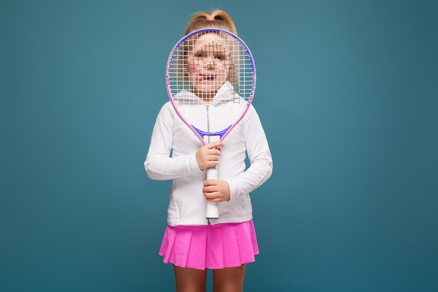 Adorable cute little girl in white shirt, white jacket and pink skirt with tennis racket