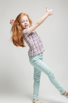Adorable cute redhead little girl in plaid shirt, bright blue trousers and white boots