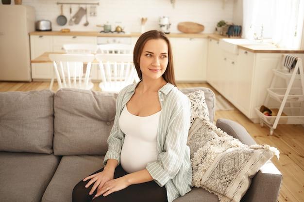 愛らしいかわいい若い妊婦ポーズ