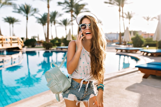 スタイリッシュなデニムショーツで愛らしいダンスガールは、彼女の親友を大きな屋外プールで一緒に泳ぐように呼びかけています