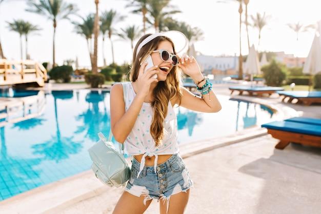 Очаровательная танцующая девушка в стильных джинсовых шортах зовет лучшую подругу вместе поплавать в большом открытом бассейне