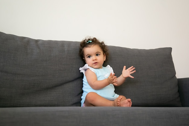 Adorable dark curly haired baby girl in pale blue cloth sitting on grey couch at home, looking away and clapping hands. kid at home and childhood concept