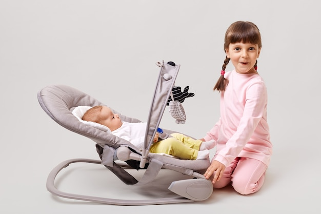 Adorable dark-haired girl with pigtails plays with newborn sister or brother who is lying in bouncer chair