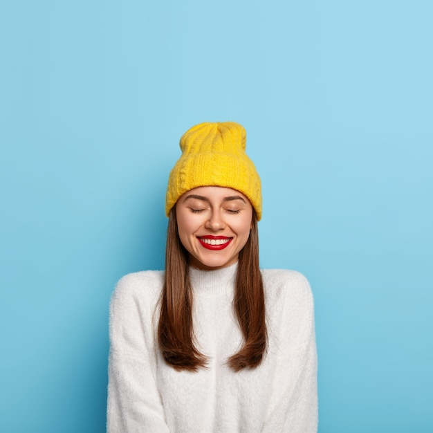 Очаровательная темноволосая женщина с минимальным макияжем, красной помадой, приятно улыбается, носит желтую шляпу и белый джемпер, изолированные на синей стене