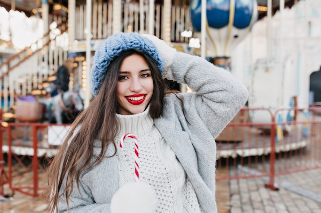겨울 주말에 놀이 공원에서 자유 시간을 보내는 사랑스러운 검은 머리 여자. 회전 목마 근처 크리스마스 사탕을 먹고 파란색 모자에 멋진 갈색 머리 아가씨의 야외 사진.