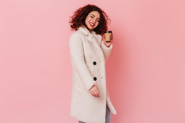 ピンクのスペースにコーヒーの段ボールのカップを保持している明るいウールのコートで真っ白な笑顔の愛らしい黒髪の女性。